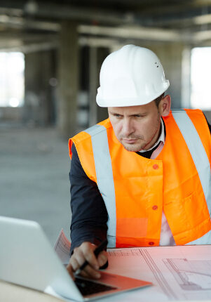 Portrait of development supervisor wearing protective vest and helmet over formal suit  proofing blueprints using laptop computer inside unfinished building